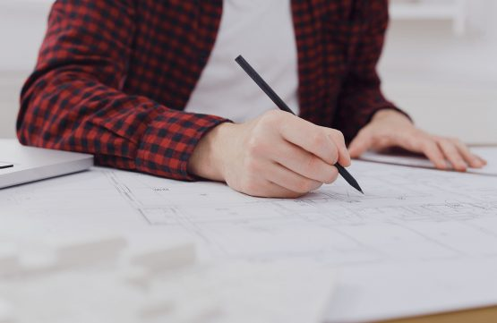 young-architect-working-with-blueprints-in-the-1